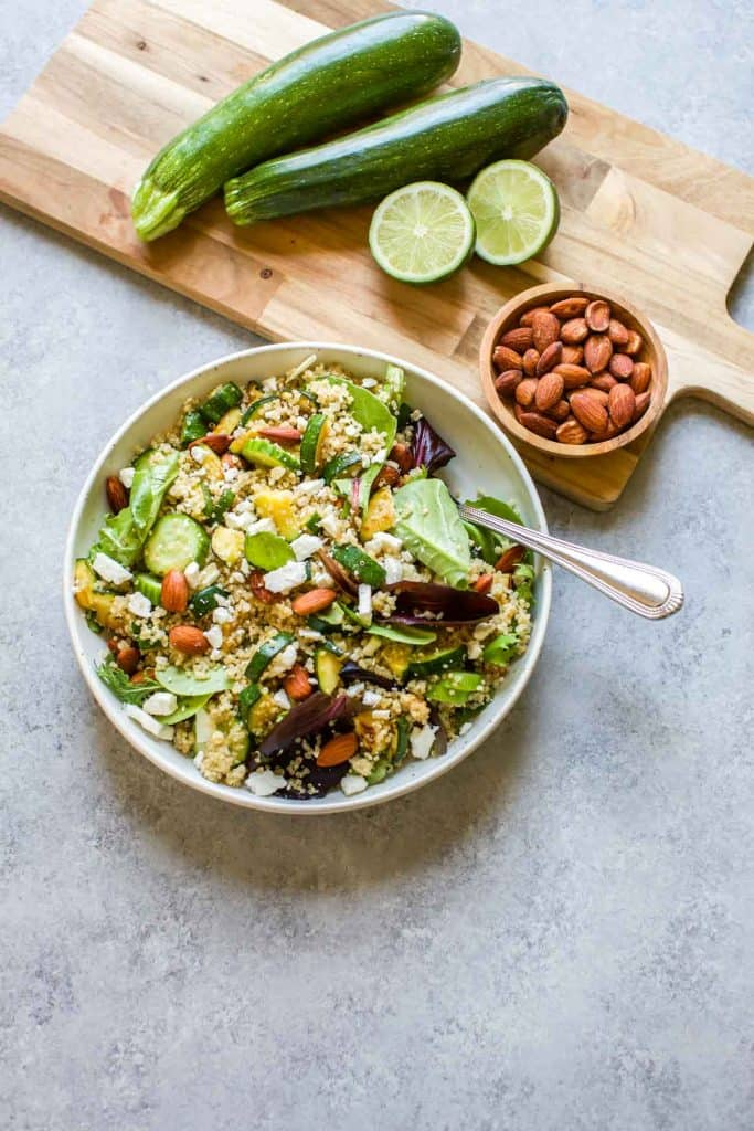 quinoa salad with zucchini , almonds and limes on the side