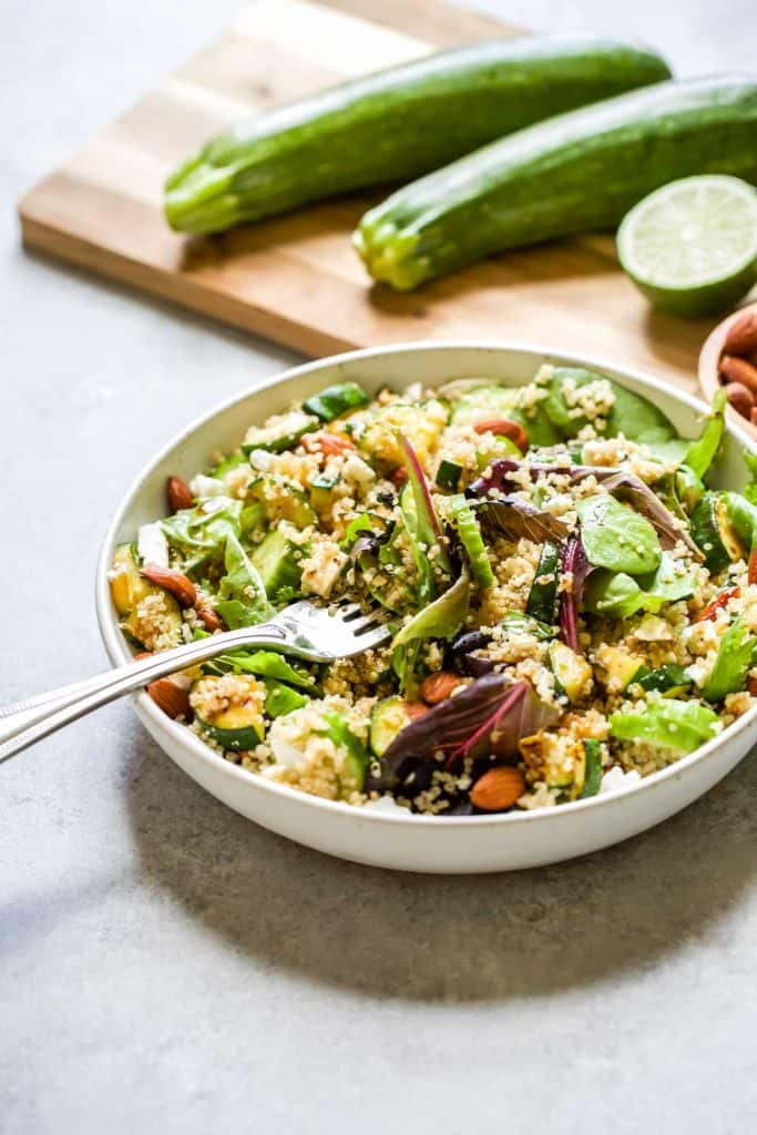 quinoa salad with greens, zucchini, cucumbers, almonds and feta