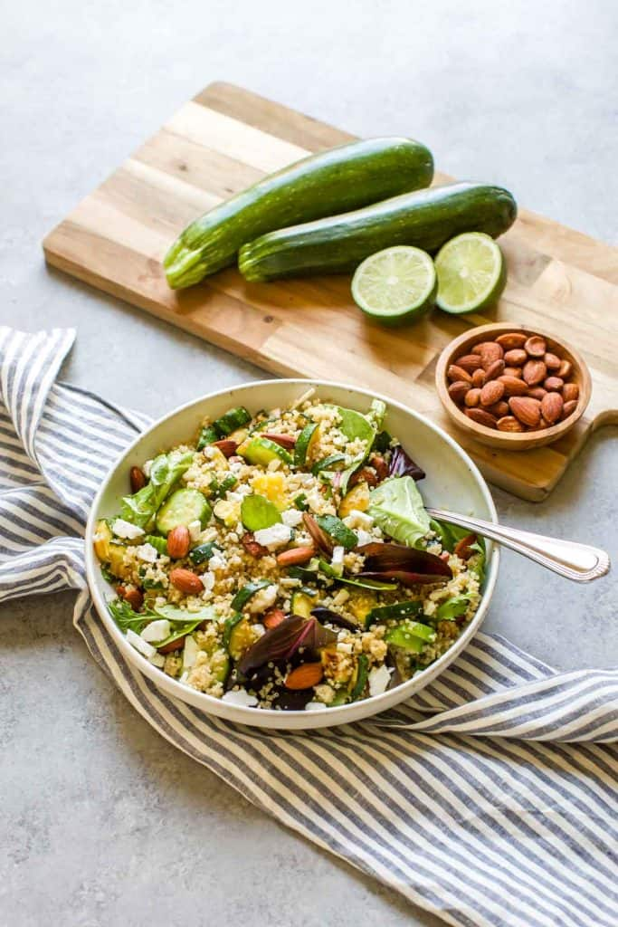 quinoa salad in a white bowl with a fork