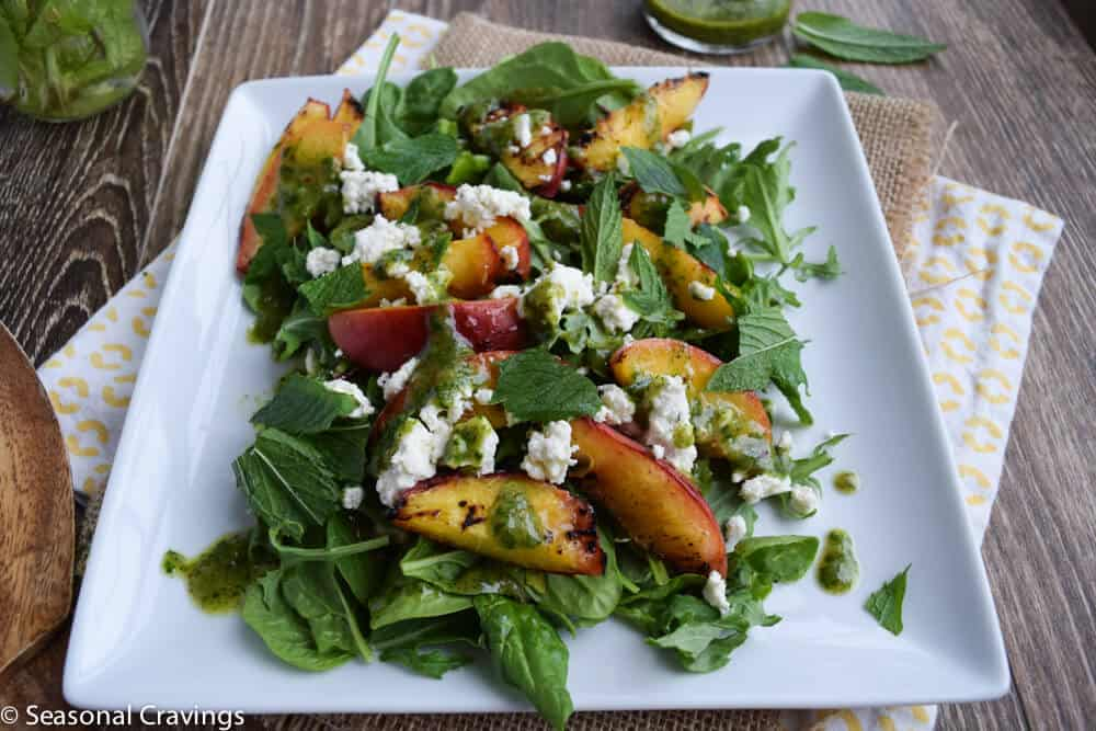 Grilled Peach Salad with mint dressing on a white plate