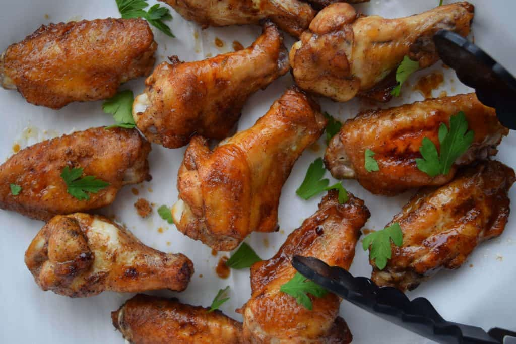 Easy Five Spice Chicken Wings on parchment with black tongs