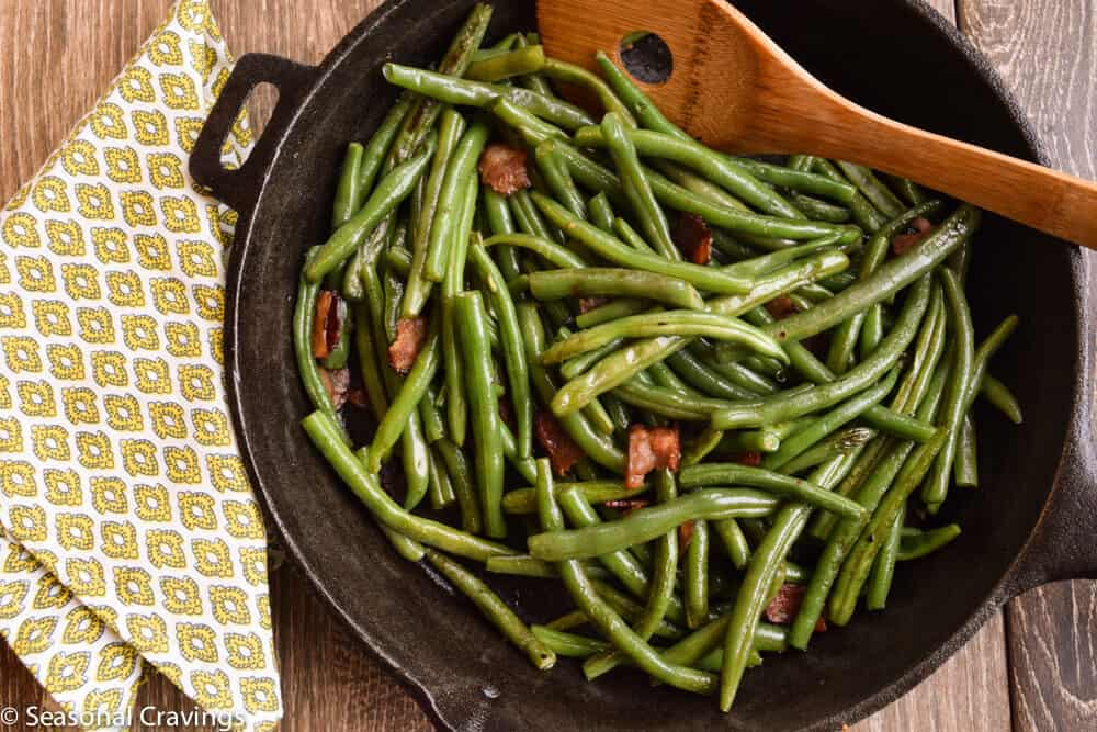Green Beans With Bacon with a wooden spoon