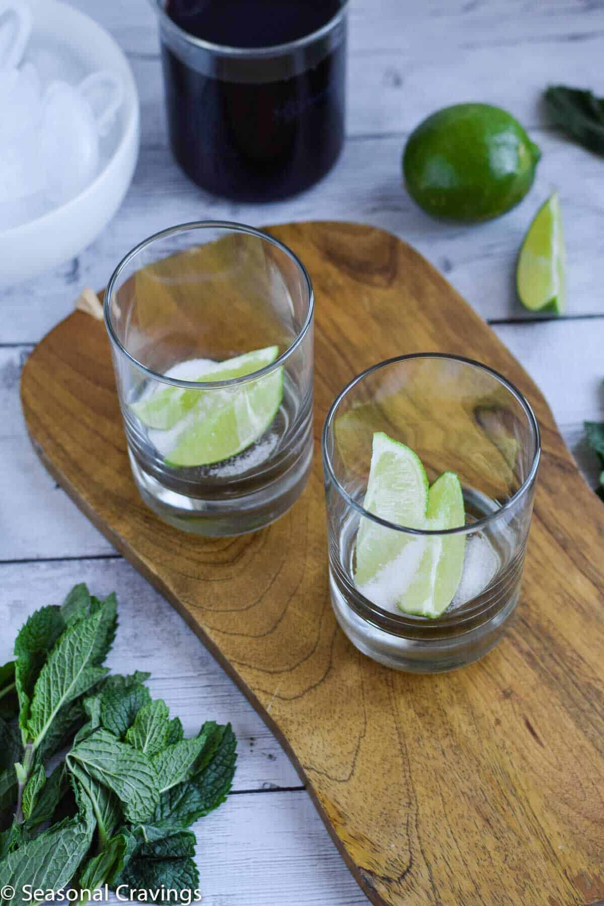 Easy Pomegranate Mojito with lime and sugar in glasses on a cutting board