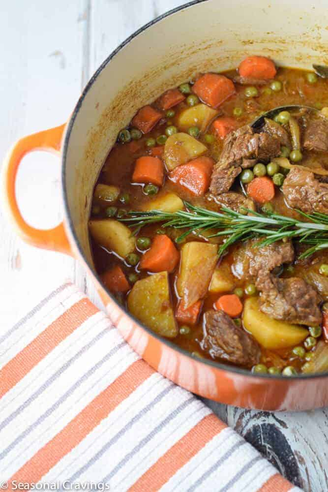 Apple Cider Beef Stew with carrots, potatoes, peas and rosemary in an orange pot