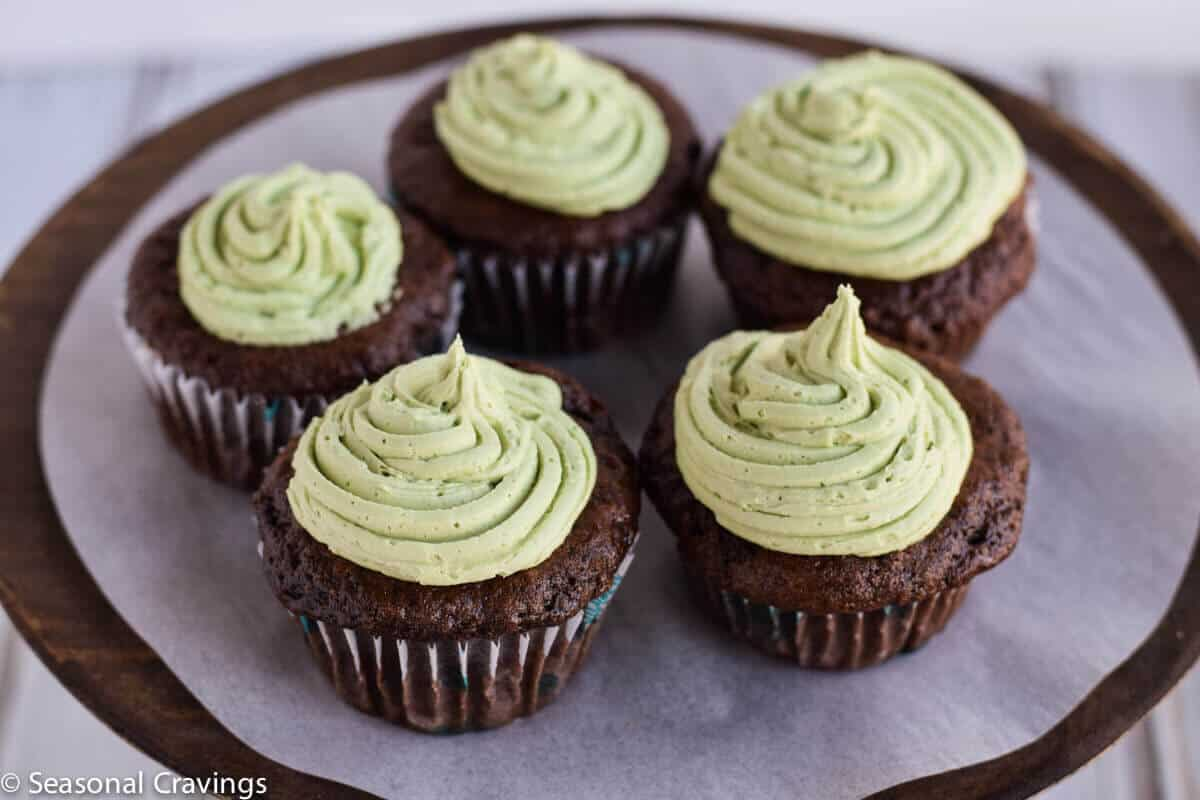 gluten free chocolate cupcakes with green buttercream frosting on a cake stand