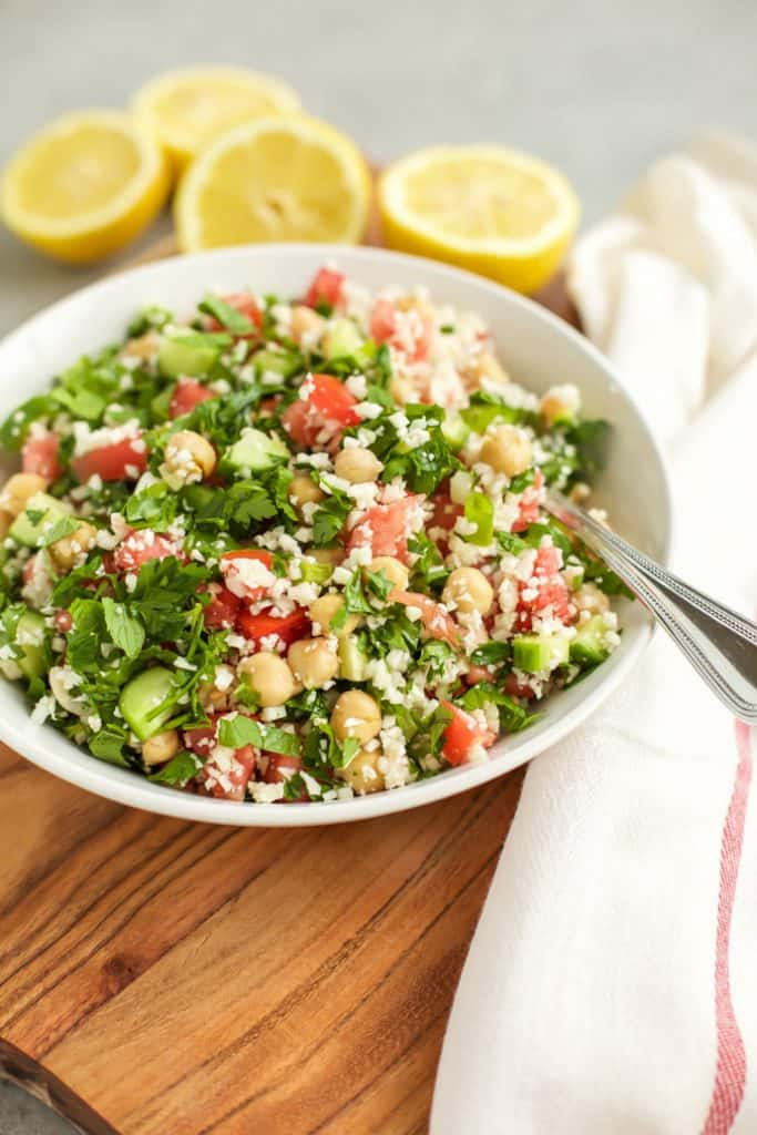 Cauliflower Tabbouleh on a white plate with lemons