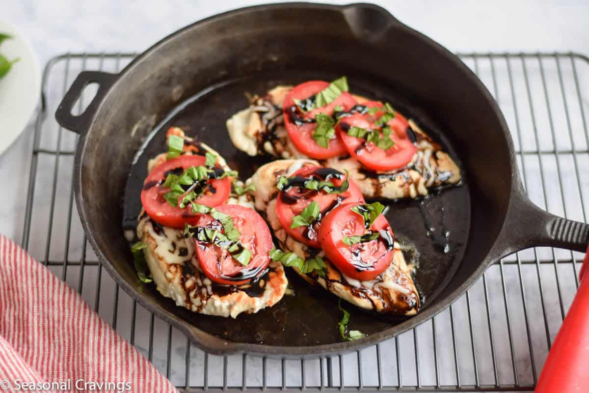 Caprese Chicken with balsamic reduction in cast iron skillet