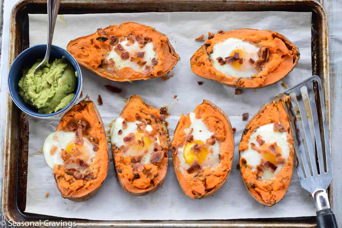 Baked Sweet Potatoes with Egg topped with bacon and guacamole on the side