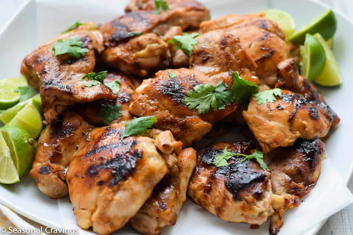 Ginger Honey Glazed Chicken on white plate with limes and parsley