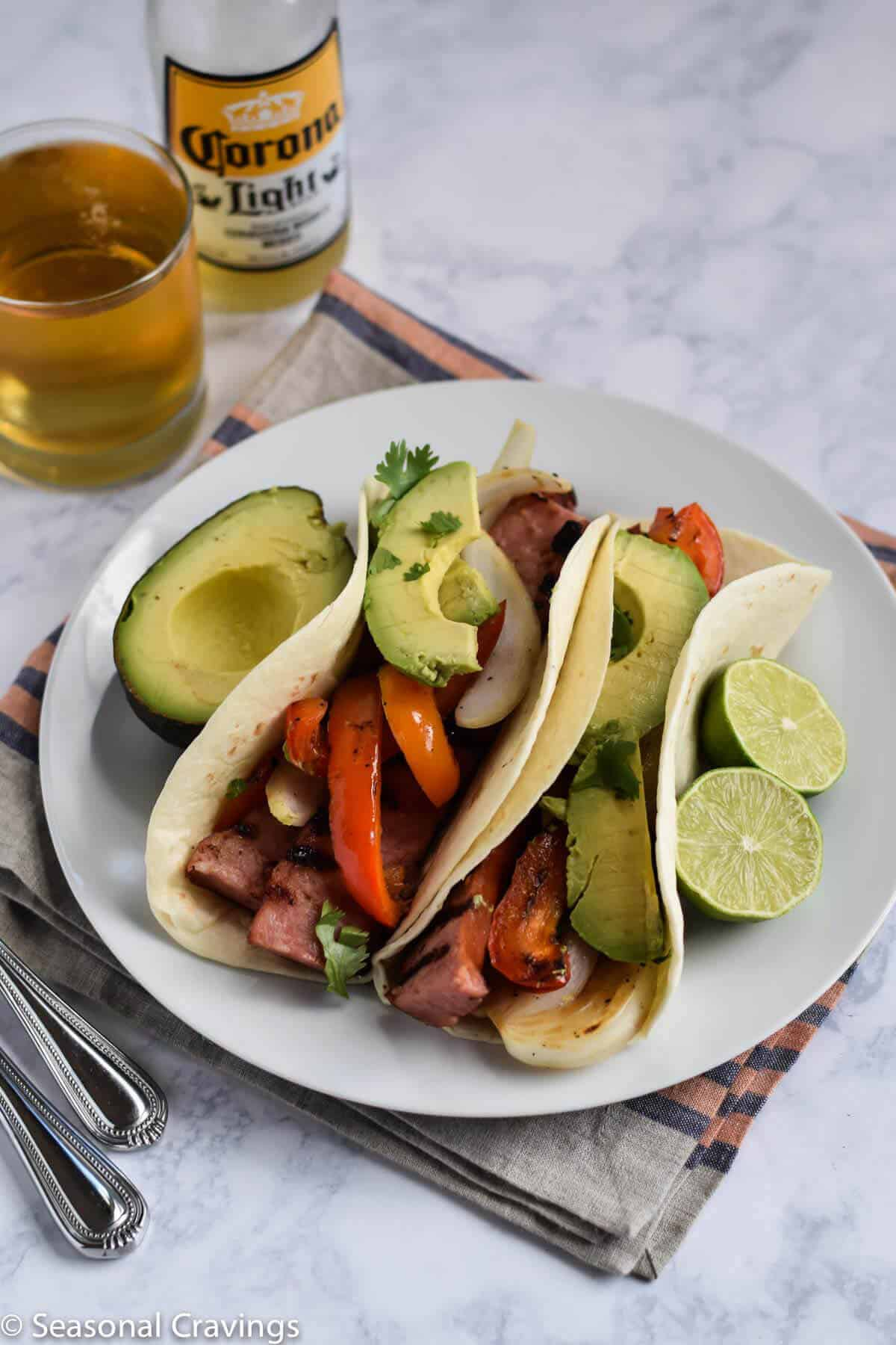 Grilled Sausage Tacos on a white plate with avocado slices