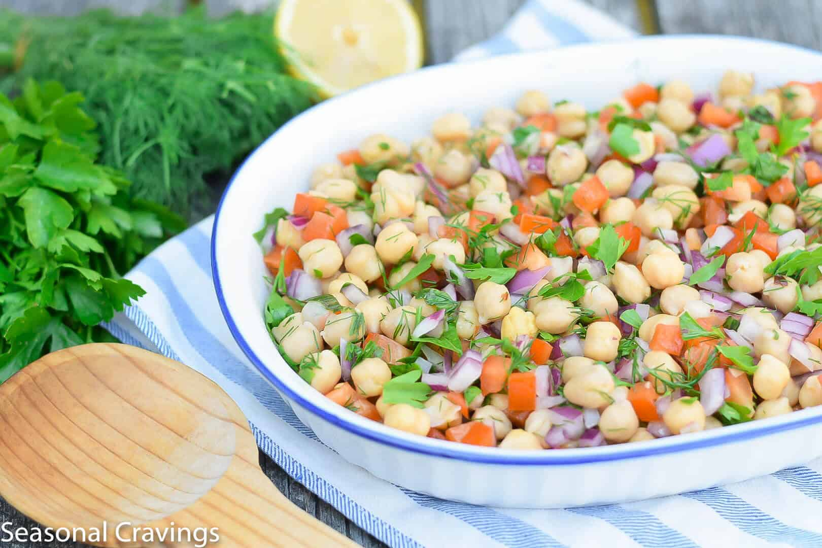 Summer Chickpea Salad with a wooden spoon in a white bowl
