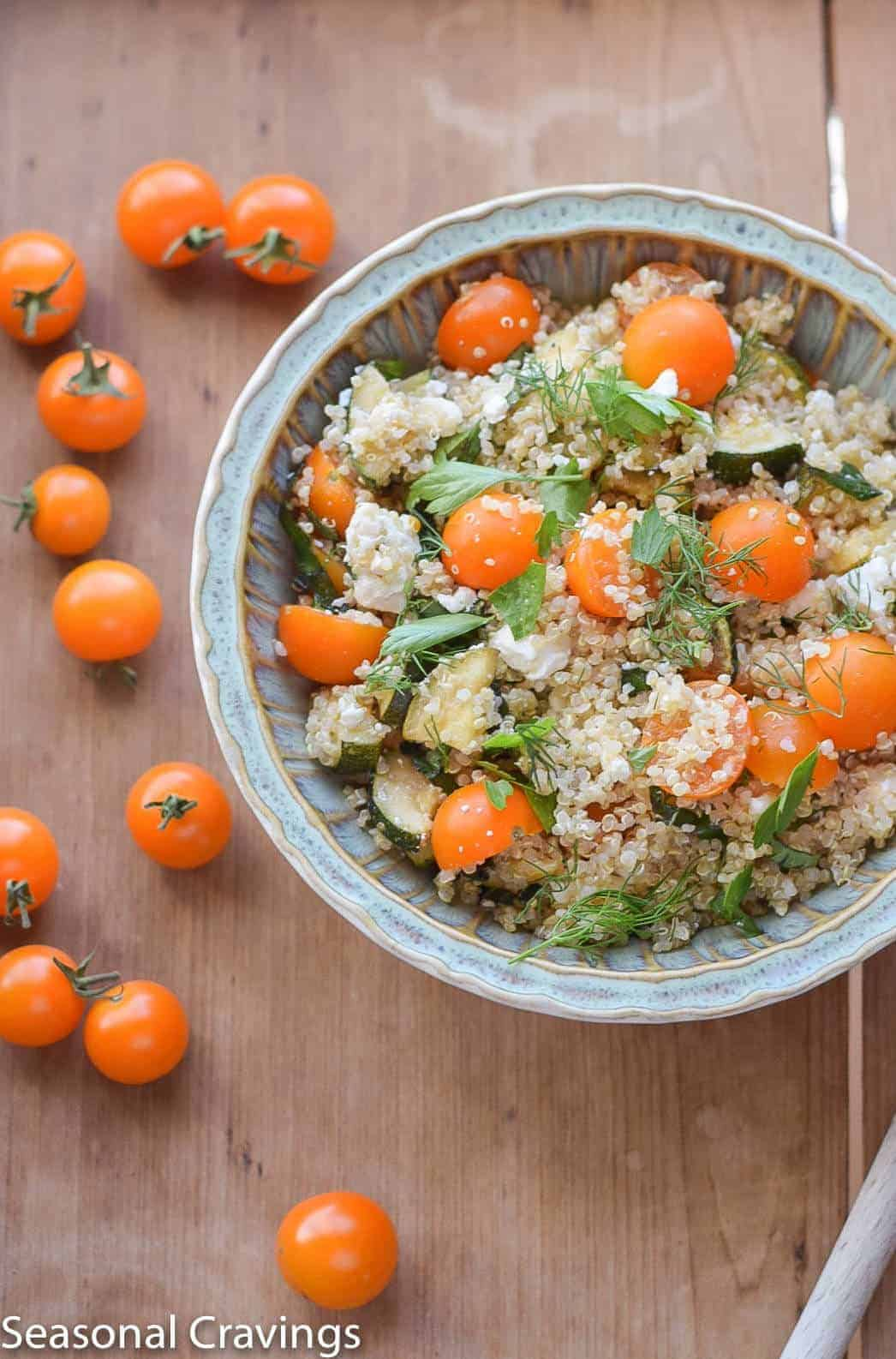 Quinoa with Zucchini and Tomatoes in a blue bowl with orange tomatoes on the side