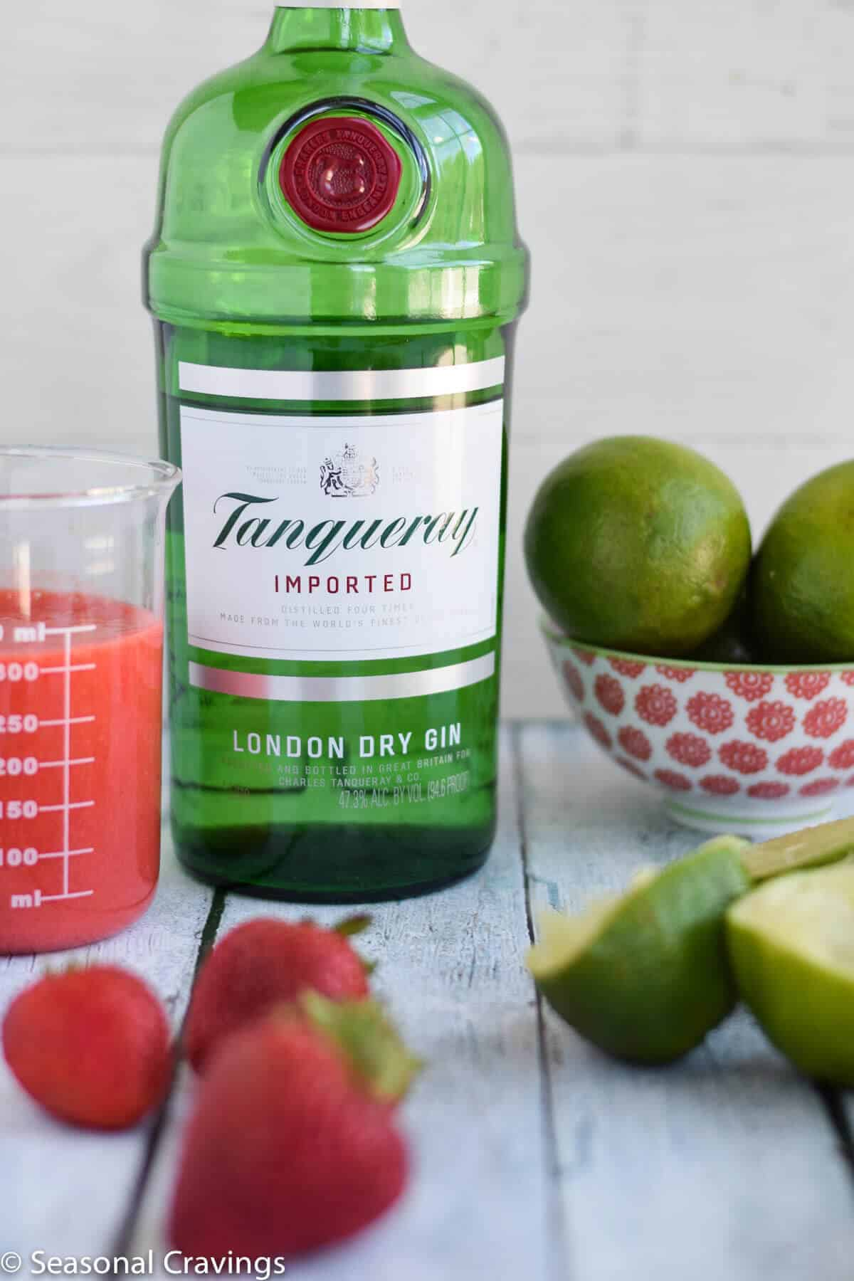 Strawberry Lime Gin Rickey with limes and strawberries and a bottle of gin