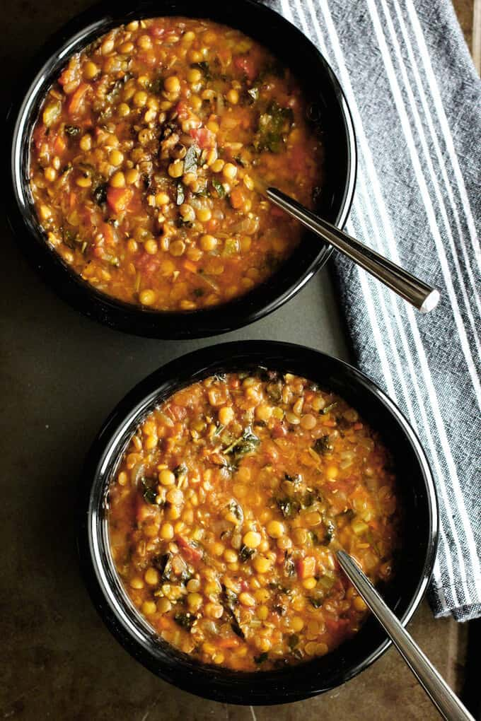 Lentil and Kale Soup in two black bowls with spoons