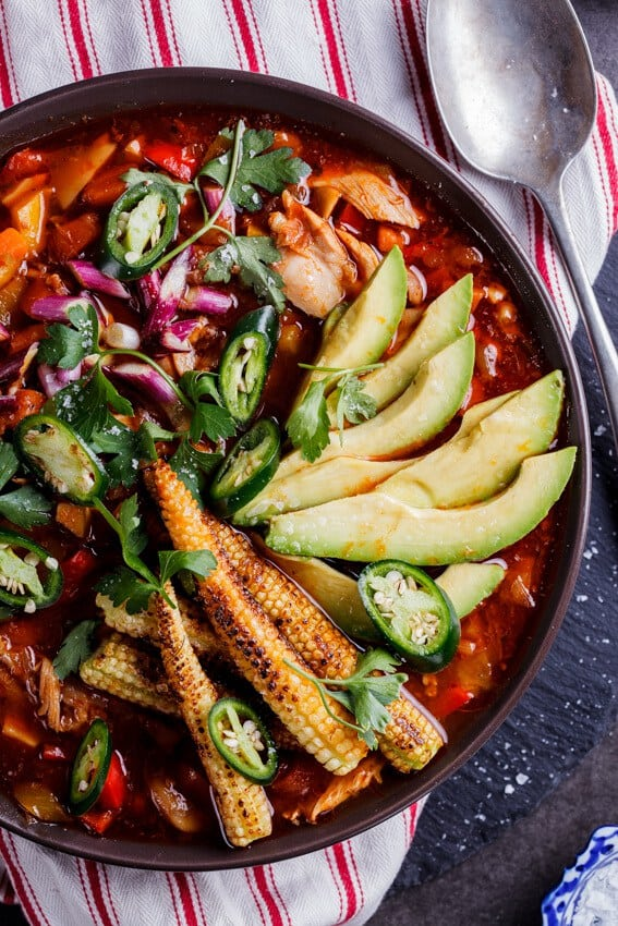 Mexican Chicken Soup with Charred Baby Corn with avocado in a bowl