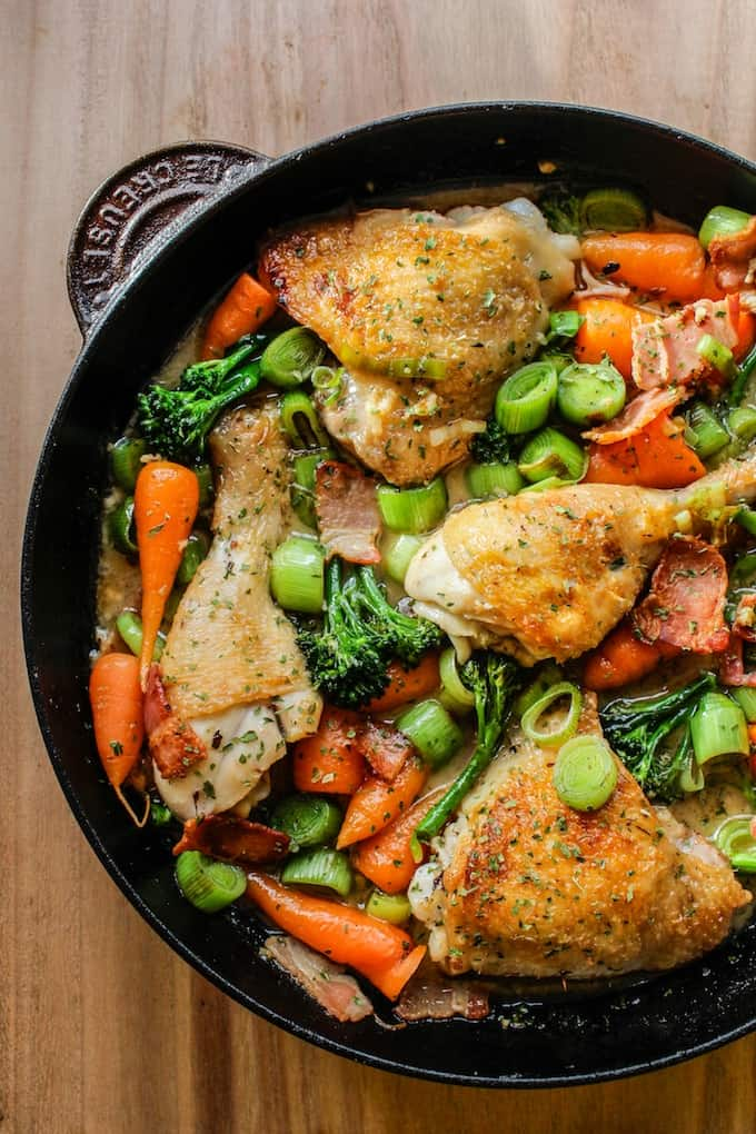 White Wine Braised Chicken with carrots, broccoli and onions in a cast iron skillet