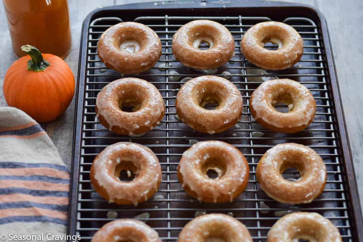 Gluten Free Apple Cider Doughnuts on a cooling rack with glaze