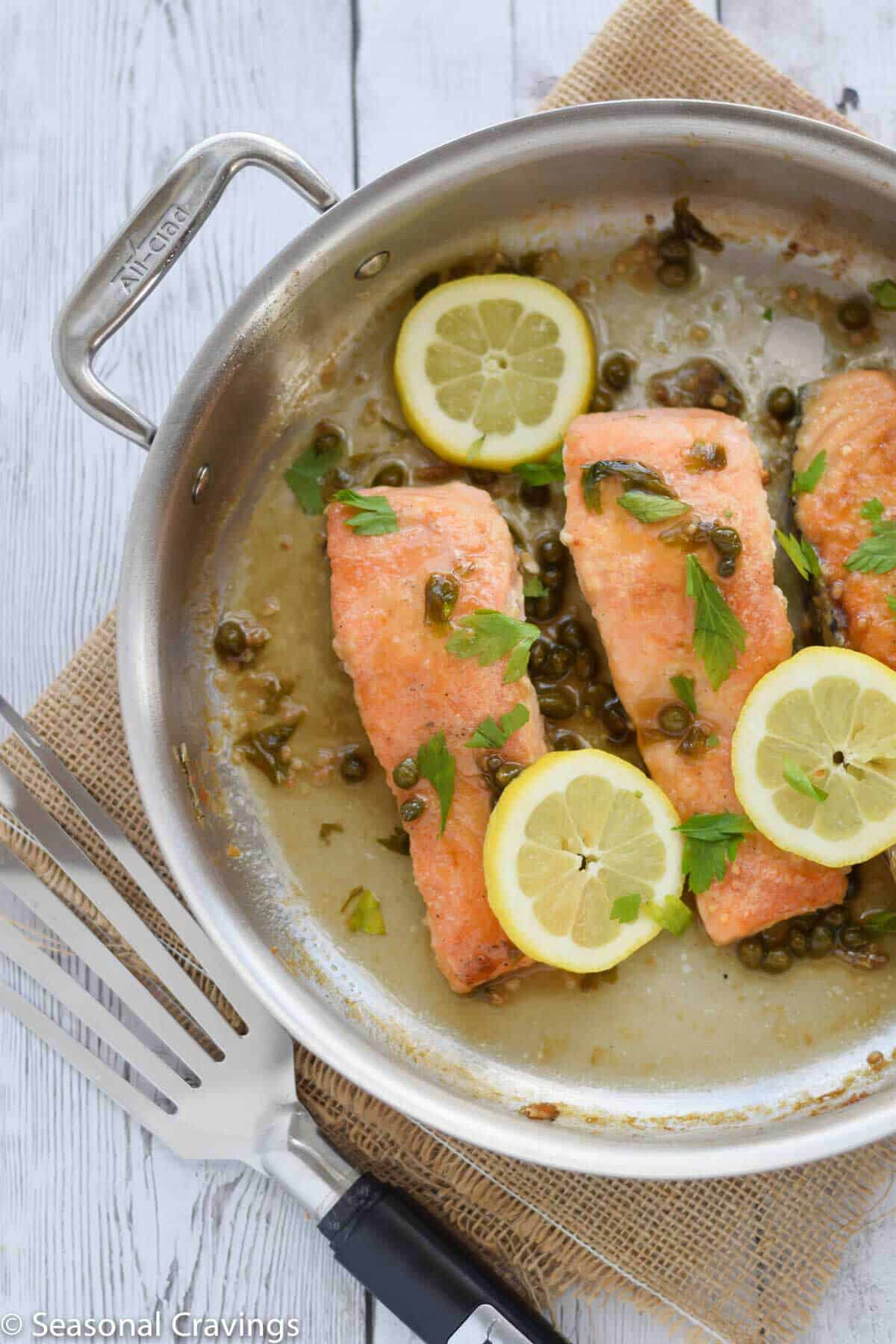 Gluten Free Salmon Piccata with lemon and parsley in a pan with spatula