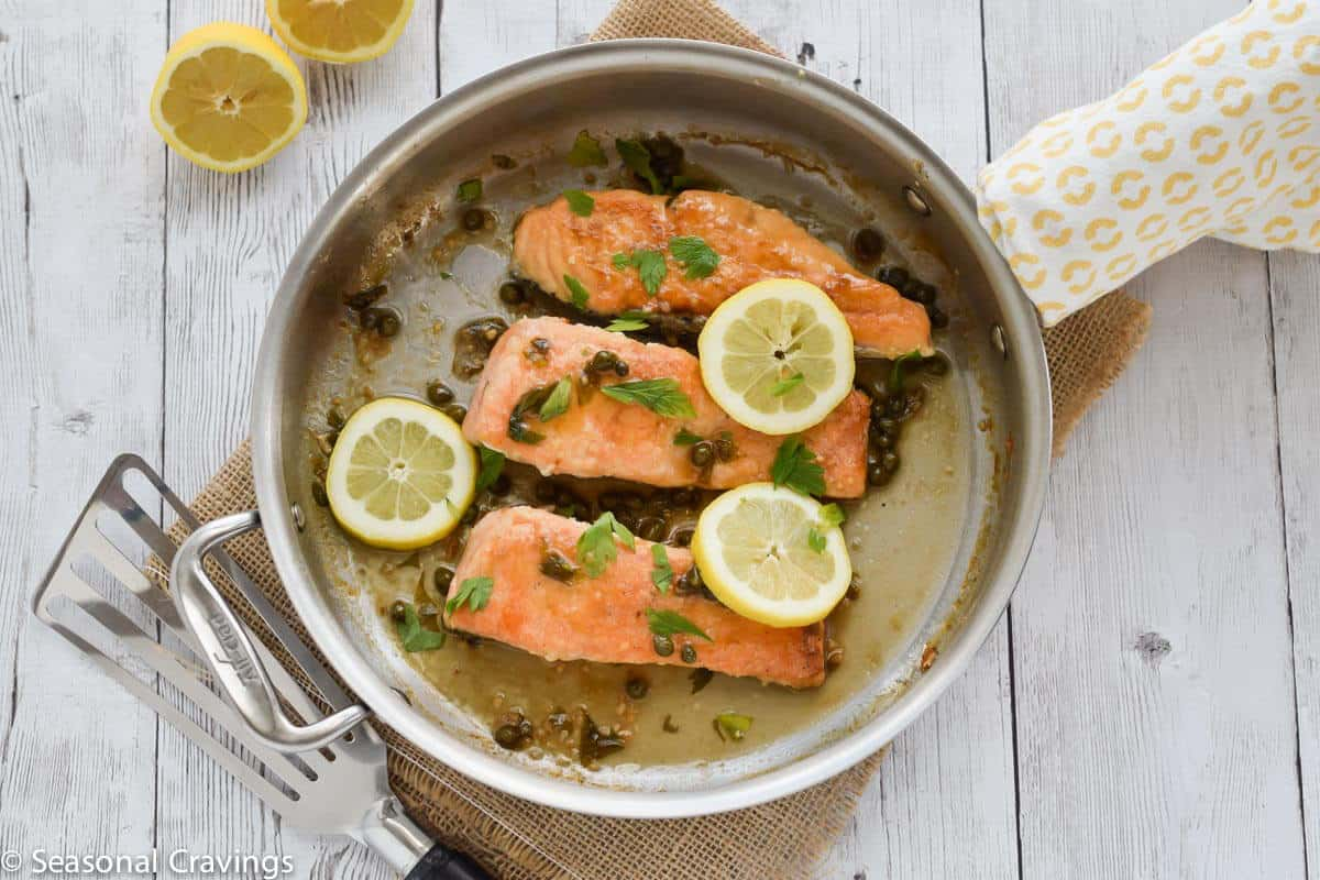 Gluten Free Salmon Piccata with lemon, capers and parsley in a skillet on white table
