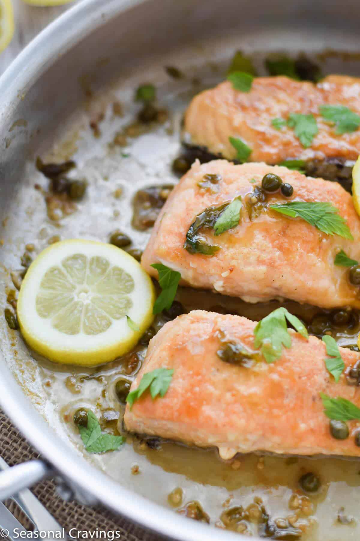 Close up of Gluten Free Salmon Piccata with lemon, capers and parsley in a white wine sauce
