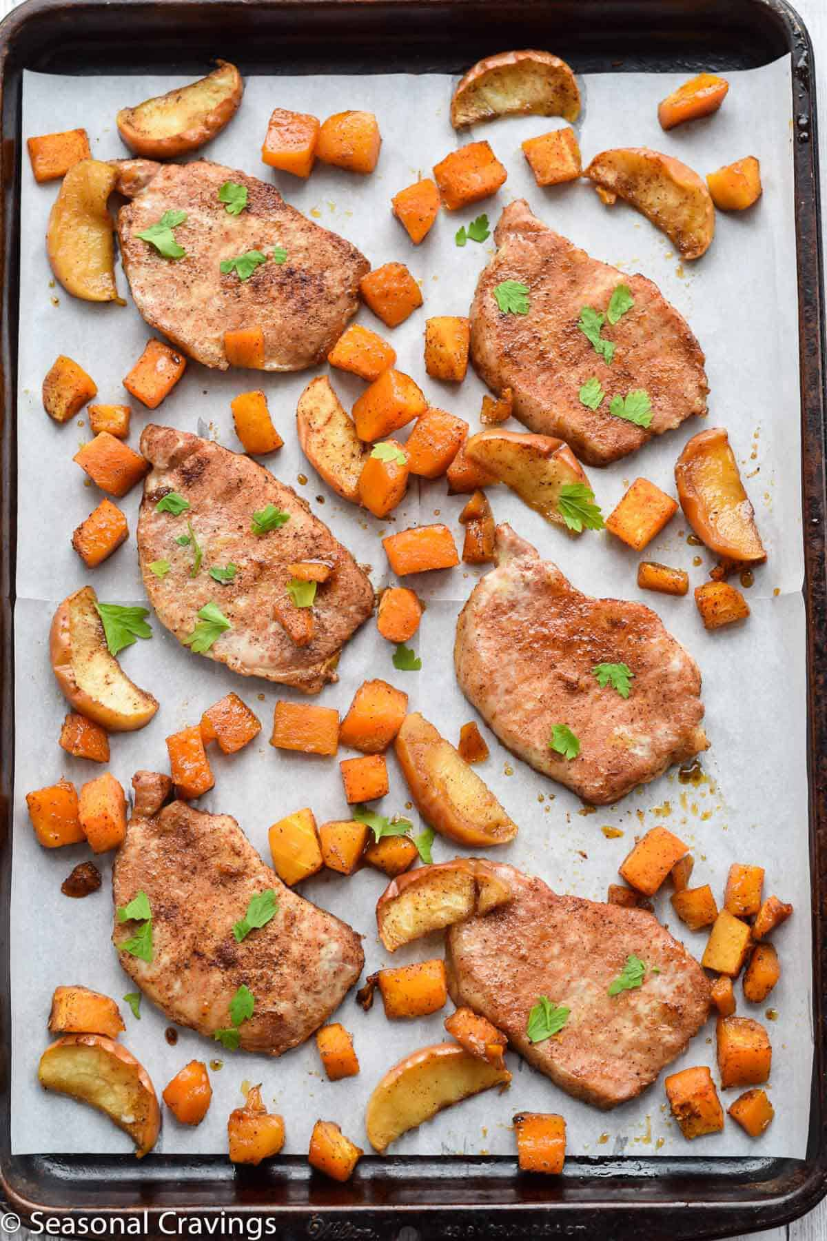 Sheet Pan Brown Sugar Pork Chops on parchment paper with parsley