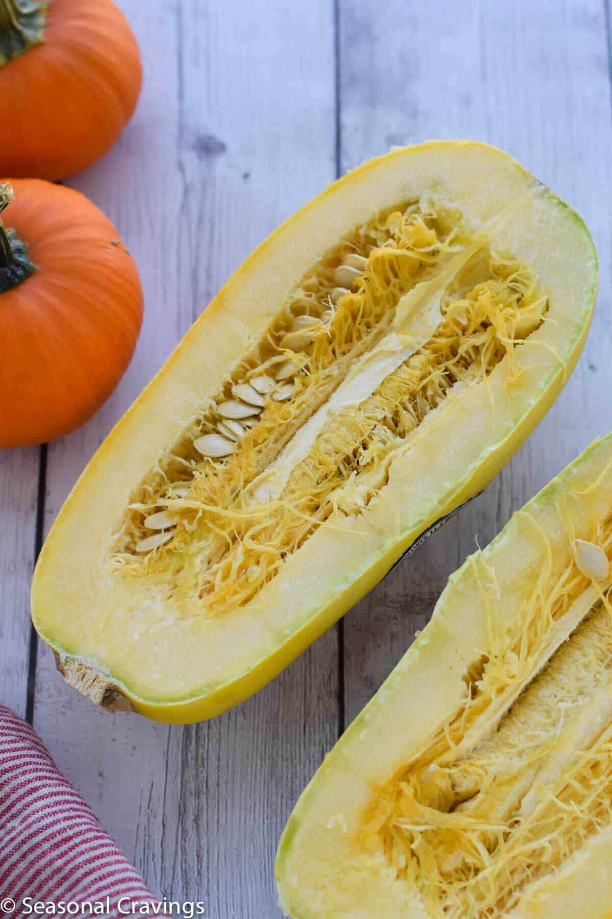 Chicken Taco Spaghetti Squash cut in half with two pumpkins
