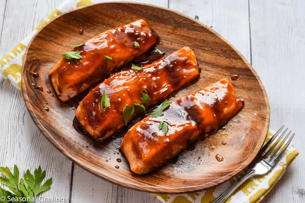 baked teriyaki glazed salmon with sweet sticky glaze and parsley garnish