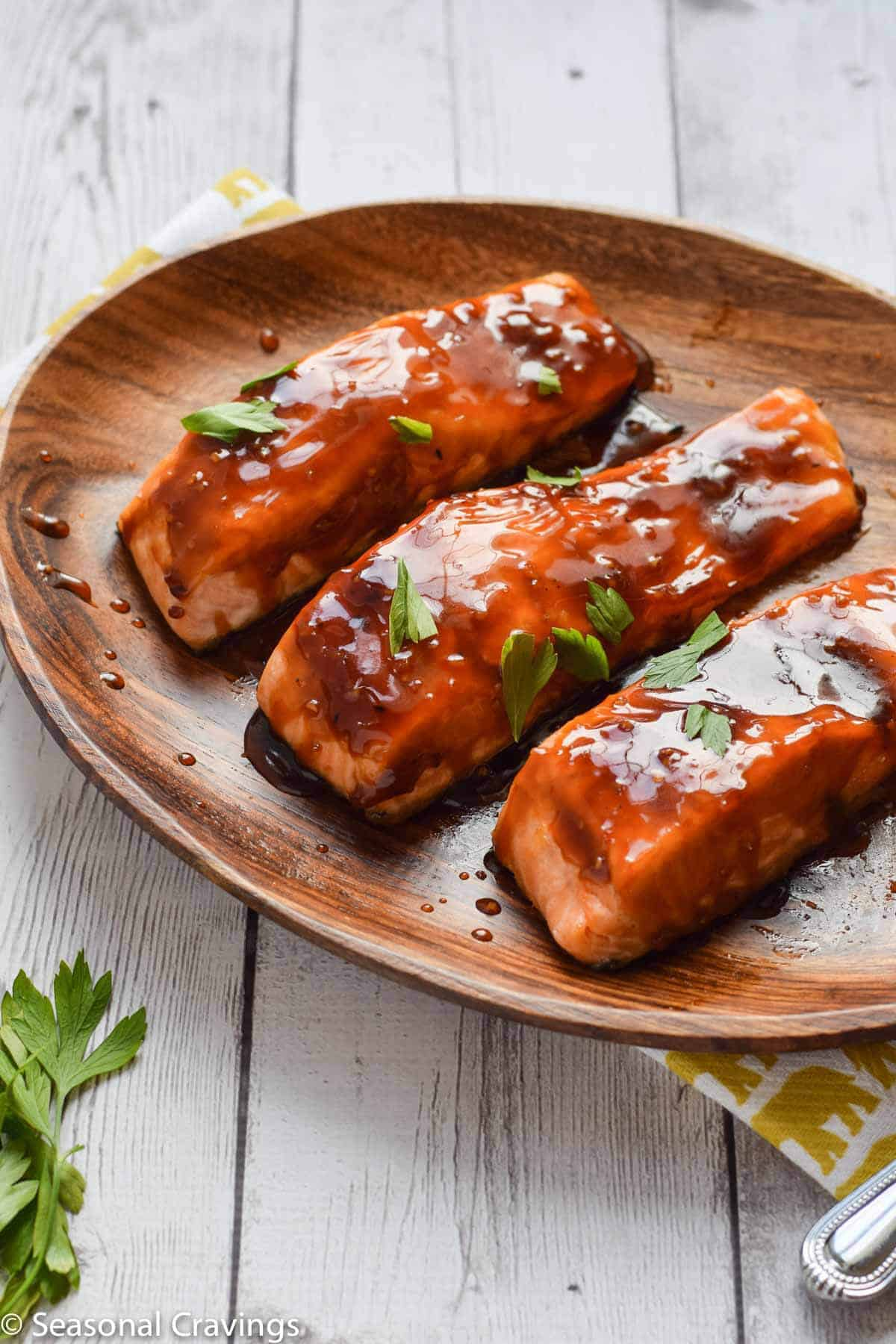 Baked Teriyaki Salmon with sweet sticky glaze on a wooden plate