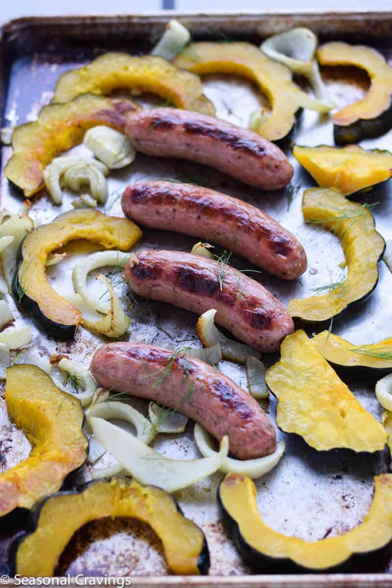 Sheet Pan Sausage and Acorn Squash and fennel with fresh dill on a sheet pan