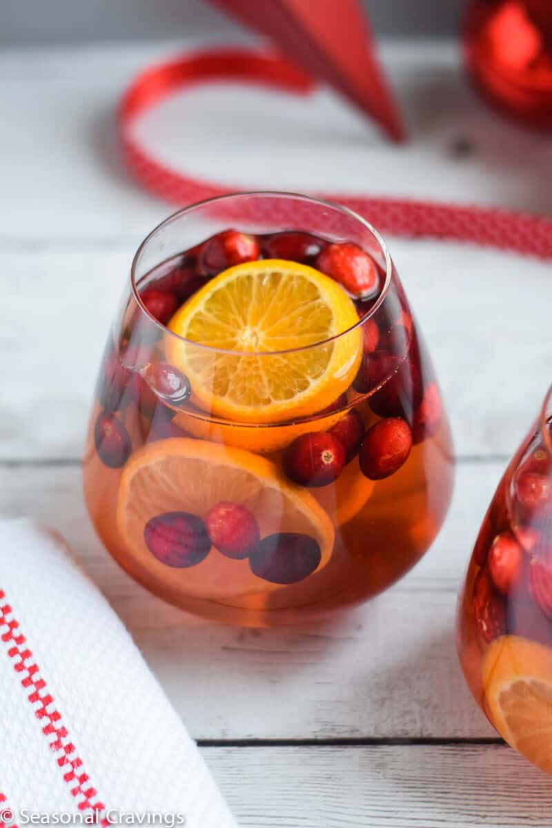 Five Ingredient White Sangria in a glass with oranges and cranberries