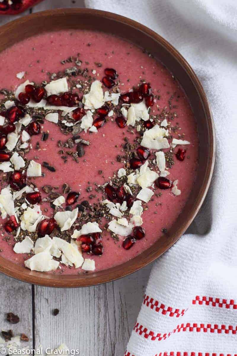 pomegranate smoothie in a brown bowl with toppings