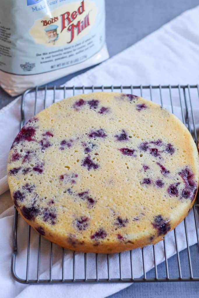 Gluten Free Lemon Blueberry Cake one layer on a cooling rack