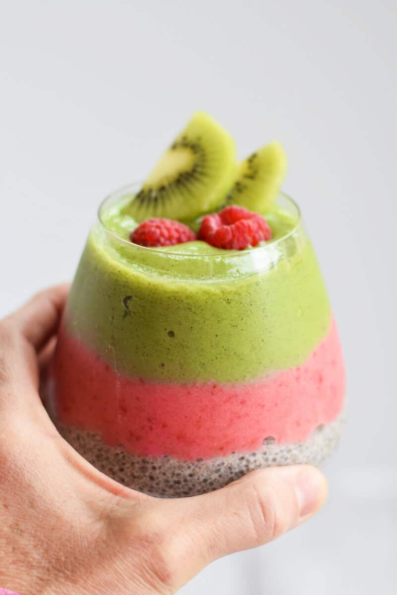 Kiwi and Raspberry Chia Pudding with a hand