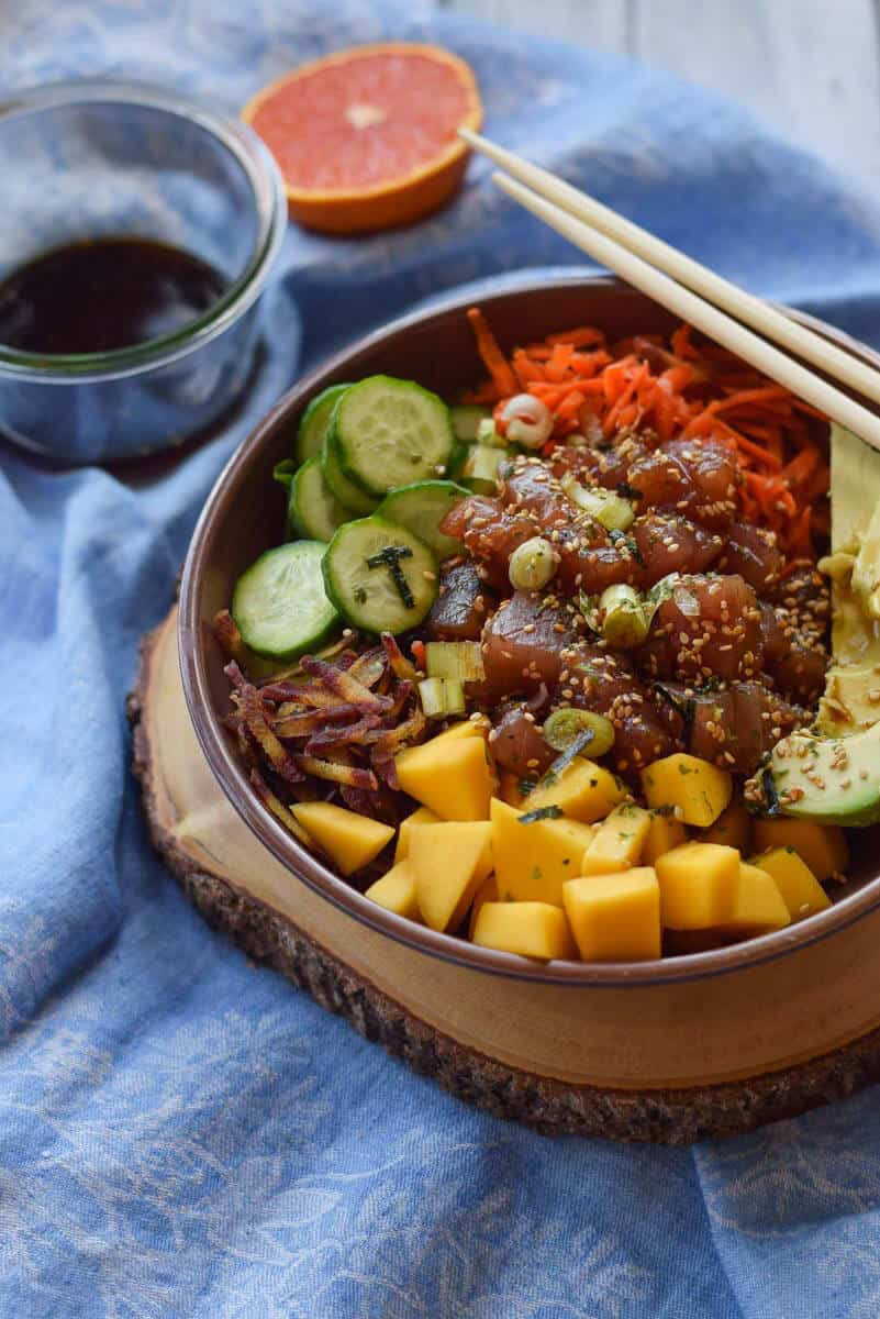 Tuna Poke Bowl with Mango and Quinoa - Sushi grade tuna with a salty dressing and a load of veggies all layered on a bed of quinoa.