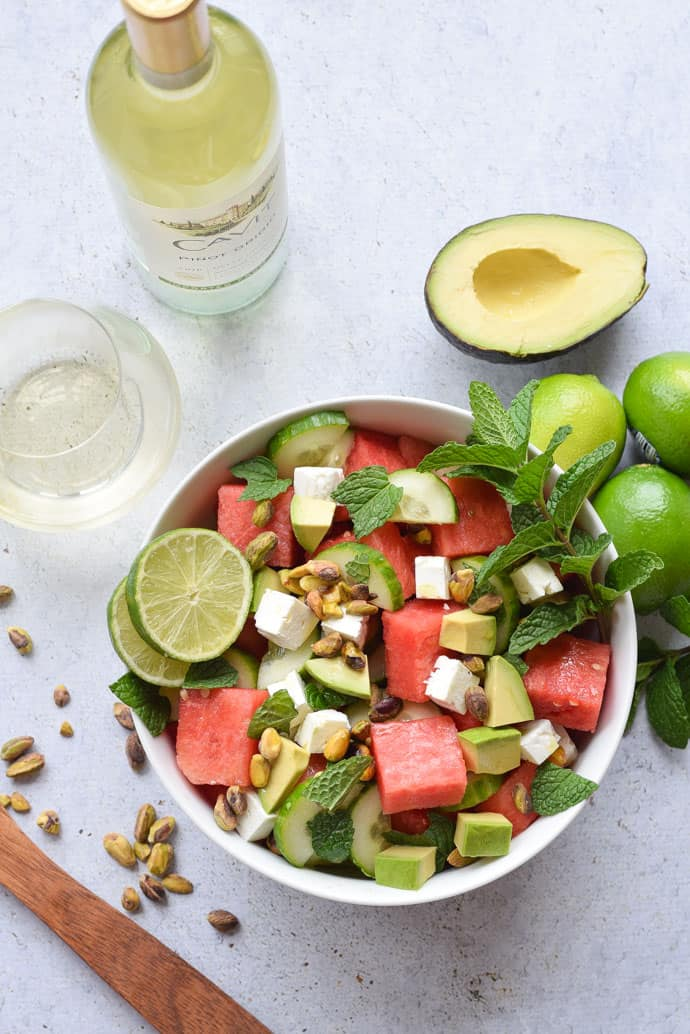 Watermelon Feta and Cucumber Salad in a white bowl with wine