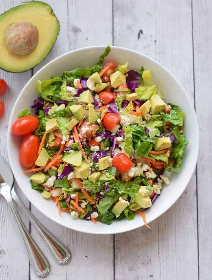 Healthy Chopped Sala with avocado in white bowl