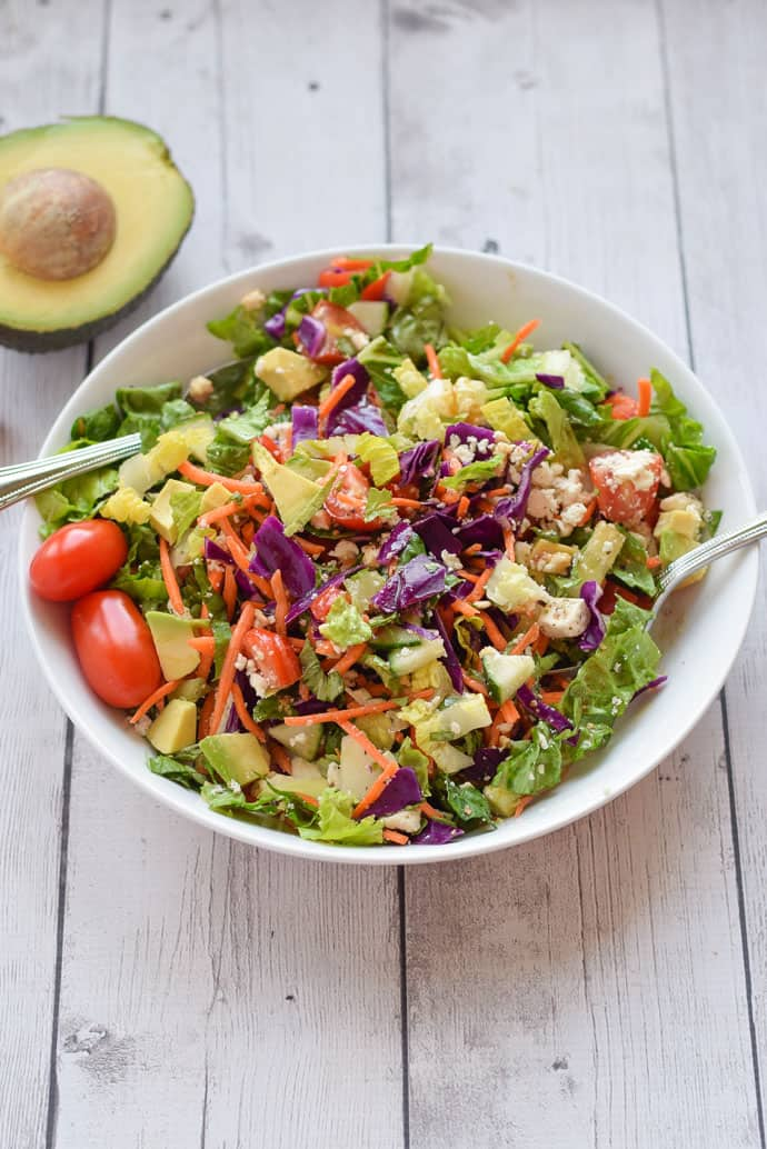 chopped salad with carrots, tomato and avocado in a white bowl