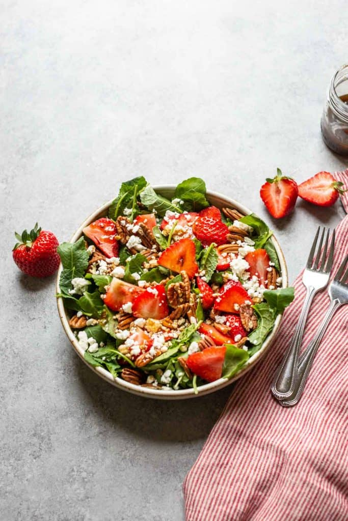 overhead shot of baby kale salad with sliced strawberries, pecans and feta cheese
