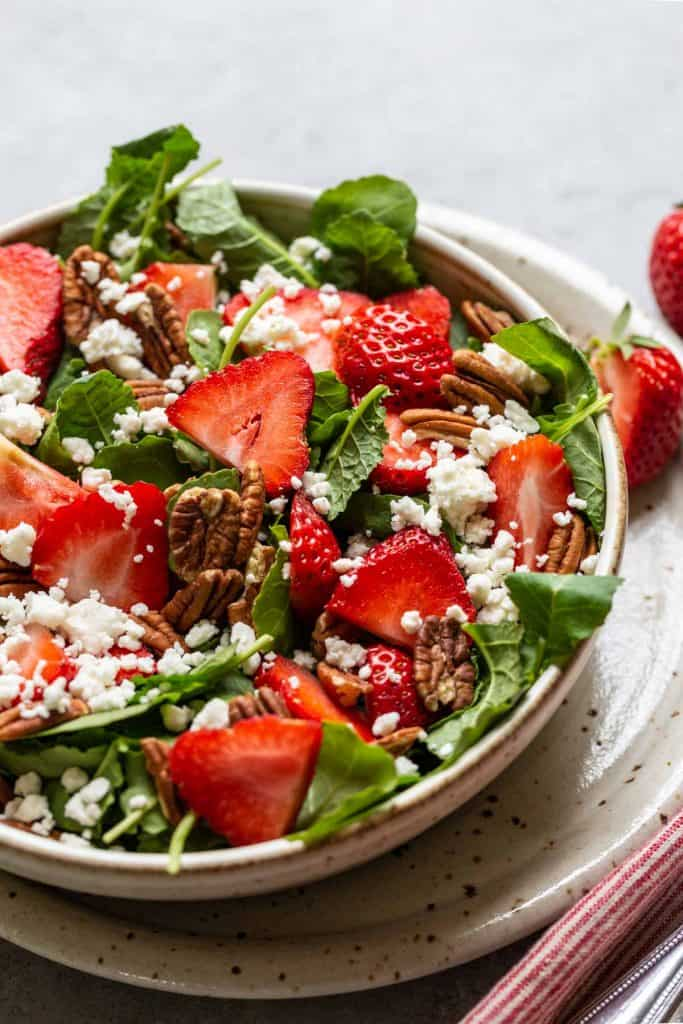 close up of kale salad with strawberries, feta and pecans