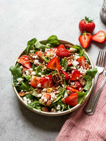 strawberry and pecan salad with feta cheese in a white bowl