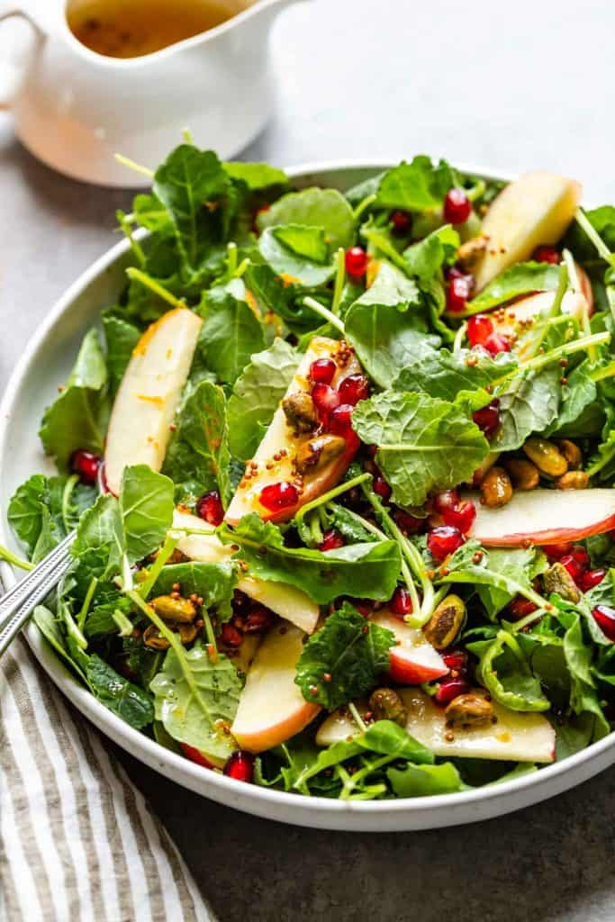 close up off kale salad with apples and pomegranate arils
