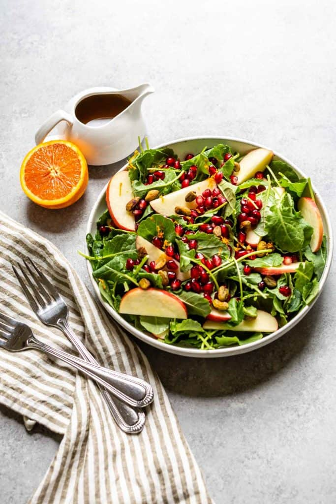 kale salad with apples and dressing on the side