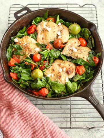 Mediterranean Skillet Chicken with Greens in a cast iron pan