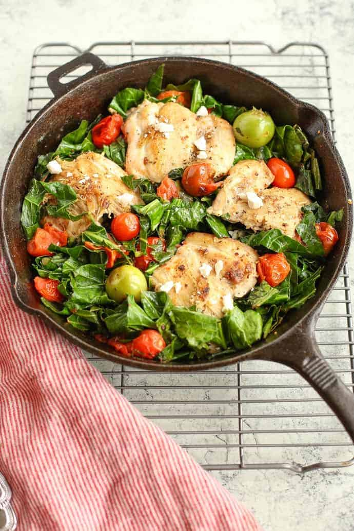 Mediterranean Skillet Chicken with Greens in a cast iron pan