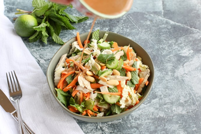 Thai Chicken Salad with dressing pouring on