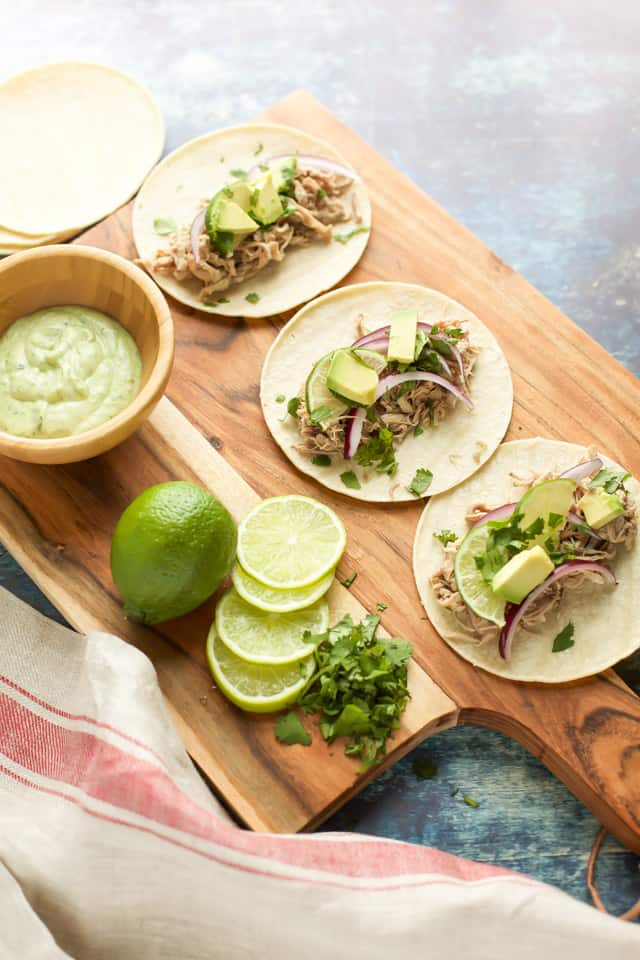 Pork Tacos Instant Pot with avocado and limes on a wooden board