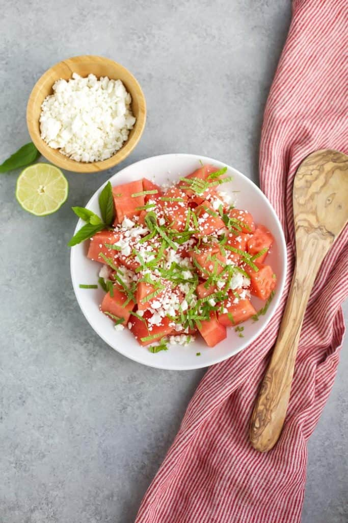 skinny watermelon feta salad in white bowl with wooden spoon
