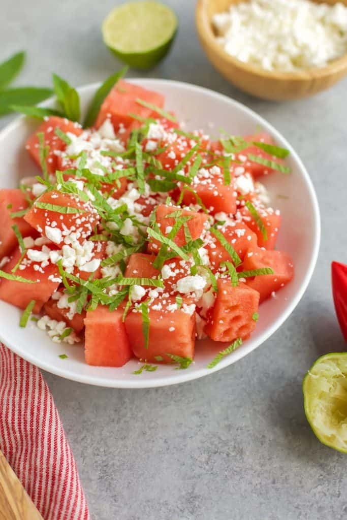 Skinny watermelon feta salad in a shite bowl with mint