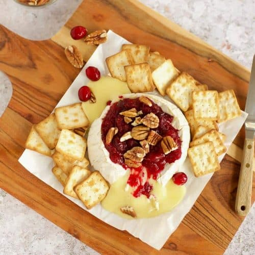 Baked Brie with Cranberry Sauce on a wooden board.