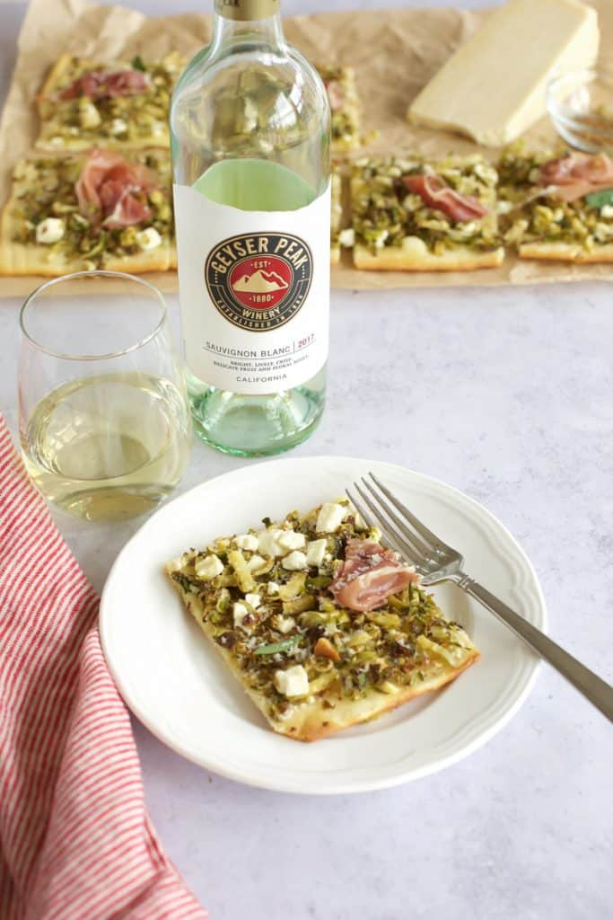 one slice of prosciutto pizza with wine